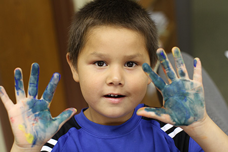 Boy with finger paint on his hands